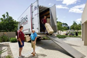Ashtons Removals staff moving boxes from the fleet truck and talking to male client