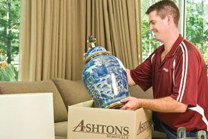 Man packing vase into moving box